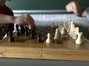 Kaksi poikaa pelaa shakkia.